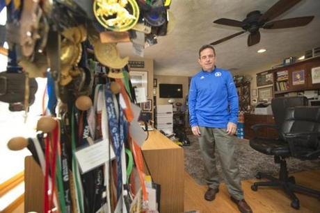 McGillivray earlier this year at his home office in North Andover, which is filled with trophies and medals from some of his 140-plus marathons.