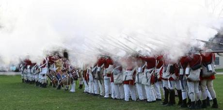 A cloud of smoke engulfs British soldiers as they fire on the Lexington Militia during the reenactment.