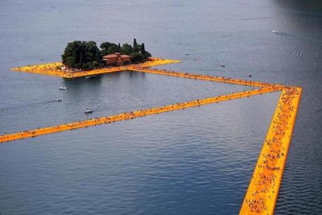 People walk on the monumental installation entitled 'The Floating Piers' created by artist Christo Vladimirov Javacheff on Iseo Lake, in northern Italy, on June 18, 2016. Some 200,000 floating cubes create a 3-kilometers runway connecting the village of Sulzano to the small island of Monte Isola on the Iseo Lake for a 16-day outdoor installation opening today. / AFP / MARCO BERTORELLO / RESTRICTED TO EDITORIAL USE - MANDATORY MENTION OF THE ARTIST UPON PUBLICATION - TO ILLUSTRATE THE EVENT AS SPECIFIED IN THE CAPTION (Photo credit should read MARCO BERTORELLO/AFP/Getty Images)