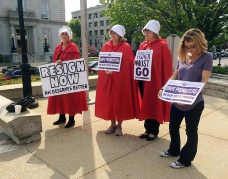 "Women dressed as characters from ""The Handmaid's Tale"" stand outside the Legislative Office Building in Concord, N.H., Wednesday, May 17, 2017, calling for the expulsion of Republican state Rep. Robert Fisher. Under fire for creating a misogynistic online forum, Fisher resigned several hours later after a committee voted to recommend the House take no action against him. (AP Photo/Holly Ramer)"