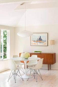 "Hovering over the Eero Saarinen dining table and Eames chairs, an iconic mid-century Nelson Saucer Bubble Pendant by Herman Miller is the only exposed light fixture in the main living area other than table lamps. ""All of the rest recede into the ceiling,"" says Alison Alessi of A3 Architects."
