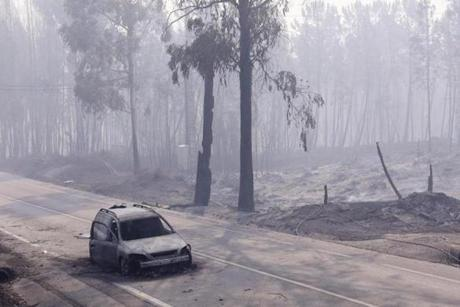 epa06034916 A burned car at N236 road between Figueiro dos Vinhos and Castanheira de Pera, near Pedrogao Grande, central Portugal, 18 June 2017. At least fifty-seven people have been killed in forest fires in central Portugal, with many being trapped in their cars as flames swept over a road on the evening of 17 June 2017. A total of 688 firefighters are providing assistance. EPA/MIGUEL A. LOPES