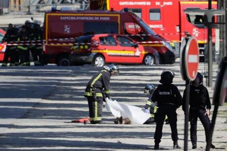 Rescuers covered the body of a man lying in a sealed off area of the Champs-Elysees avenue in Paris.