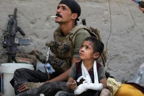 TOPSHOT - Omar, a young wounded Iraqi boy whose family was killed in the ongoing battles to oust the Islamic State (IS) group from Mosul, sits with members of the Counter Terrorism Services (CTS) as they help him to flee the Old City of Mosul on July 3, 2017. Iraqi forces have been closing in on the Old City in west Mosul for months, but the terrain combined with a large civilian population has made for an extremely difficult fight. / AFP PHOTO / AHMAD AL-RUBAYEAHMAD AL-RUBAYE/AFP/Getty Images