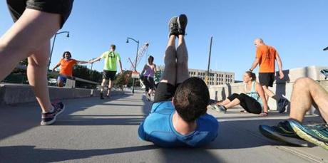 With construction cranes as a backdrop, a group took part in a circuit training session on the closed Boston University Bridge.