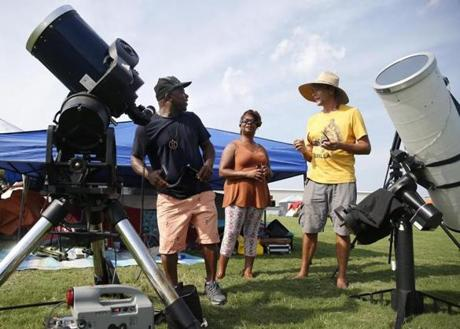 Hopkinsville, KY -- 8/19/2017 - (L-R) Locals Gary Barker and Loretta Hudson both of Hopkinsville talk with Brian Badgett, of Louisville, about his two telescopes at a makeshift campground in Hopkinsville city nearest the point of greatest eclipse. (Jessica Rinaldi/Globe Staff) Topic: 21EclipseNashville Reporter: Nestor Ramos