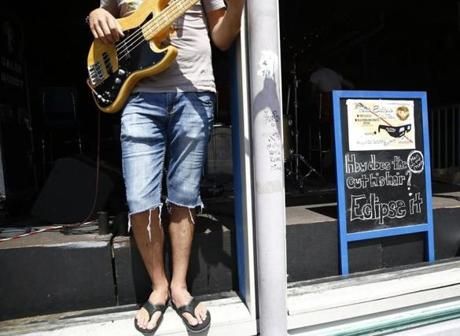 "Nashville, TN -- 8/19/2017 - Jeremy Conn, of Nashville, plays outside of the Tin Roof beside a sign that reads, ""How does the Man on the Moon cut his hair? Eclipse it."" ahead of tomorrow's total eclipse. (Jessica Rinaldi/Globe Staff) Topic: 21EclipseNashville Reporter: Nestor Ramos"