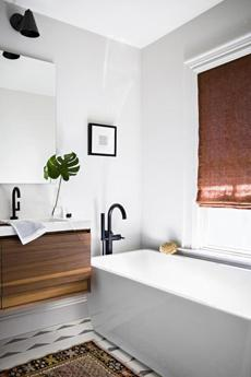 In the new master bath, the American Standard Sedona Loft soaking tub sits in the same spot as the old tub. The freestanding tub-filler fixture is by Jason Wu for Brizo, and the Cle Tile flooring has radiant heat. The subtle hand-blocked Roman shade fabric is Alamwar Textiles Anjali Creeper from  Studio Four NYC.