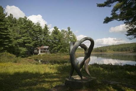 "September 7, 2017 - Shutesbury, MA - home of Julian Janowitz The ""Dancers"" sculpture on the property of Mr. Janowitz made by himself with a view of Mr. Janowitz's home in the background Julian Janowitz, 88 years old, is dying of renal failure and will donate his property on Ames Pond to Kestrel Land Trust upon his death. The property is filled with a collection of sculptures and installation art made by Mr. Janowitz who is a self taught artist. Mr. Janowitz had a professional career as a psychiatrist. Photo by Katherine Taylor for The Boston Globe"