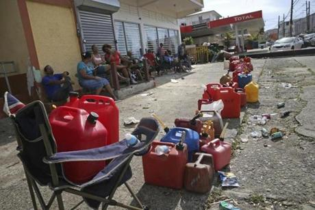 Residents lined up gas cans as they waited for a gas truck to service an empty gas station.