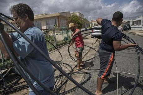 Neighbors David Riefkohl, Charles Yates and Jose Nieve cleared downed power lines from their block in Yabucoa, Puerto Rico on Sunday.