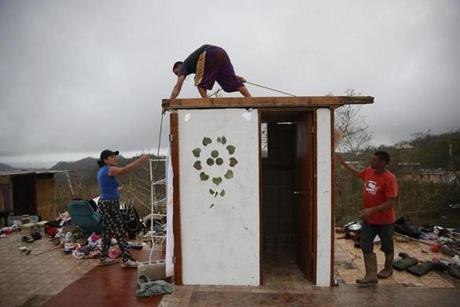 Carmen Maldonado, Jose Flores and Carlos Flores (left to right) put a temporary roof the bathroom which is all that is left of their home.