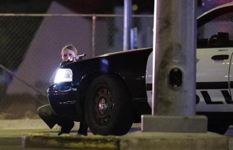 LAS VEGAS SLIDER2 A police officer takes cover behind a police vehicle during a shooting near the Mandalay Bay resort and casino on the Las Vegas Strip, Sunday, Oct. 1, 2017, in Las Vegas. (AP Photo/John Locher)