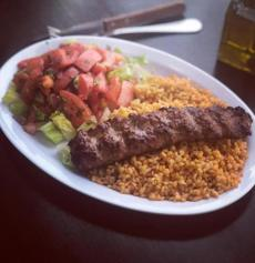 A lamb adana plate, the meat grilled and seasoned with spicy red bell peppers and served on a bed of bulgur and shepherd's salad.