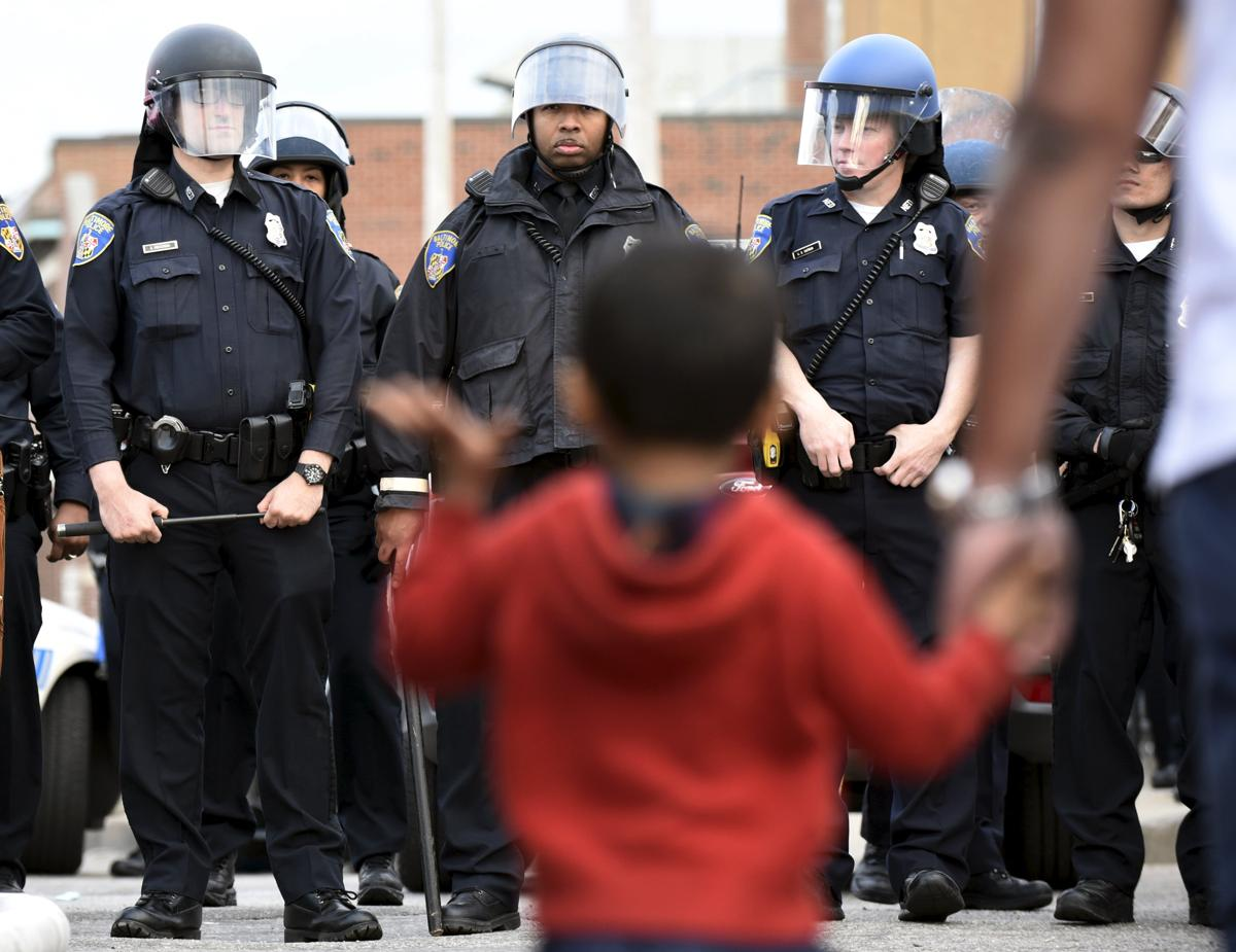 Baltimore police officers in riot gear push protestors back along - 10