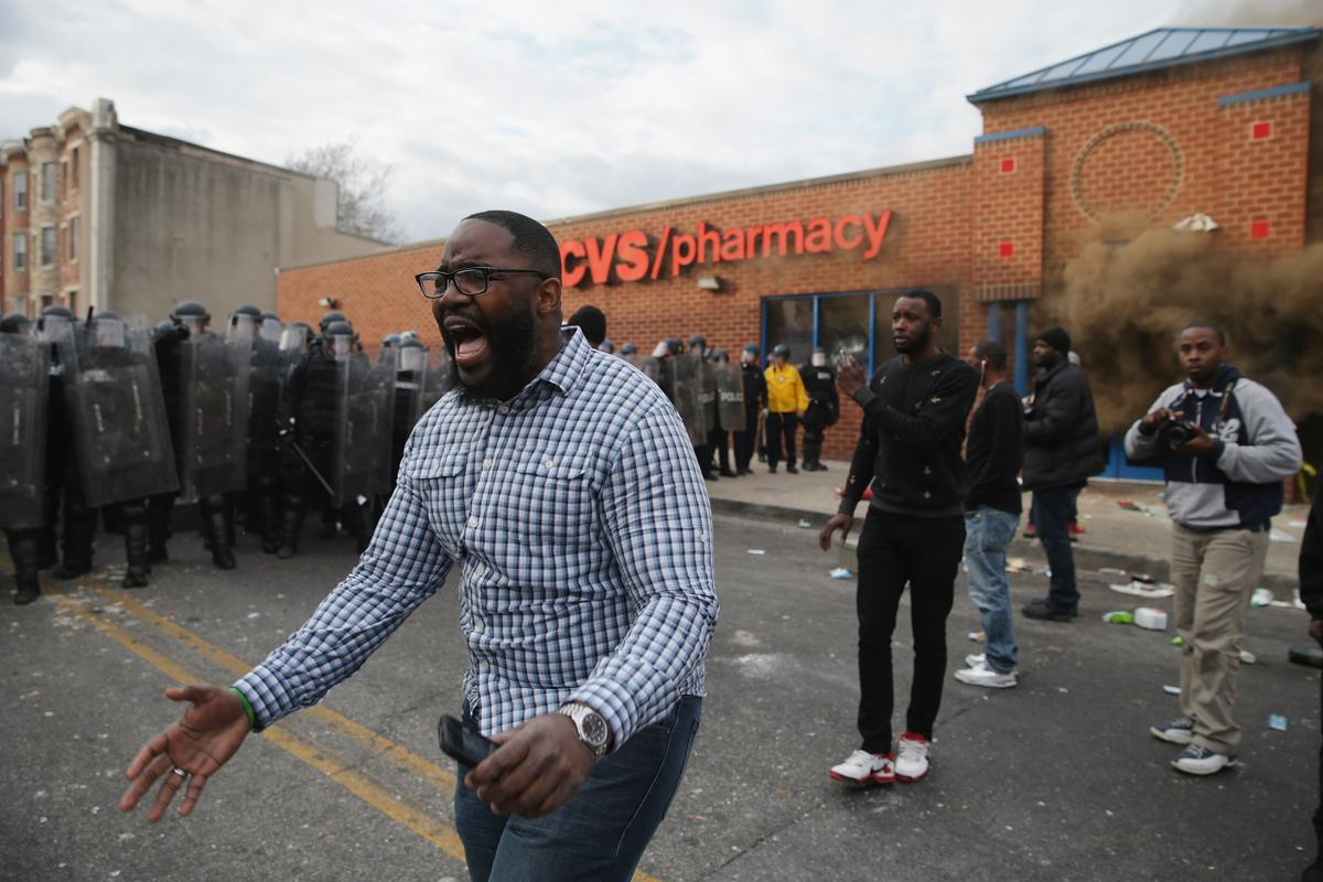 Baltimore police officers in riot gear push protestors back along - 9
