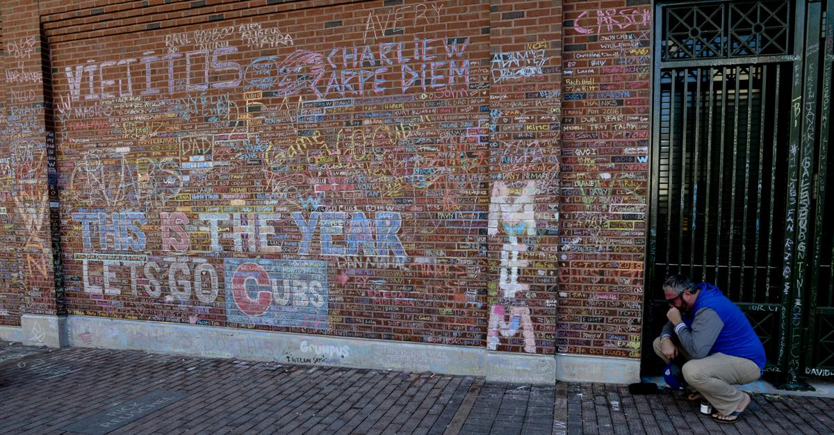 cubs fans write their names in chalk on brick wall of wrigley field