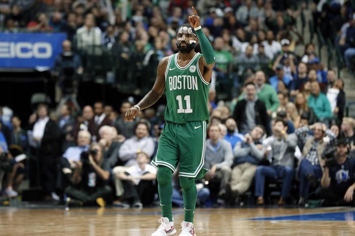 Boston Celtics' Kyrie Irving (11) celebrates sinking a basket against the  Dallas Mavericks