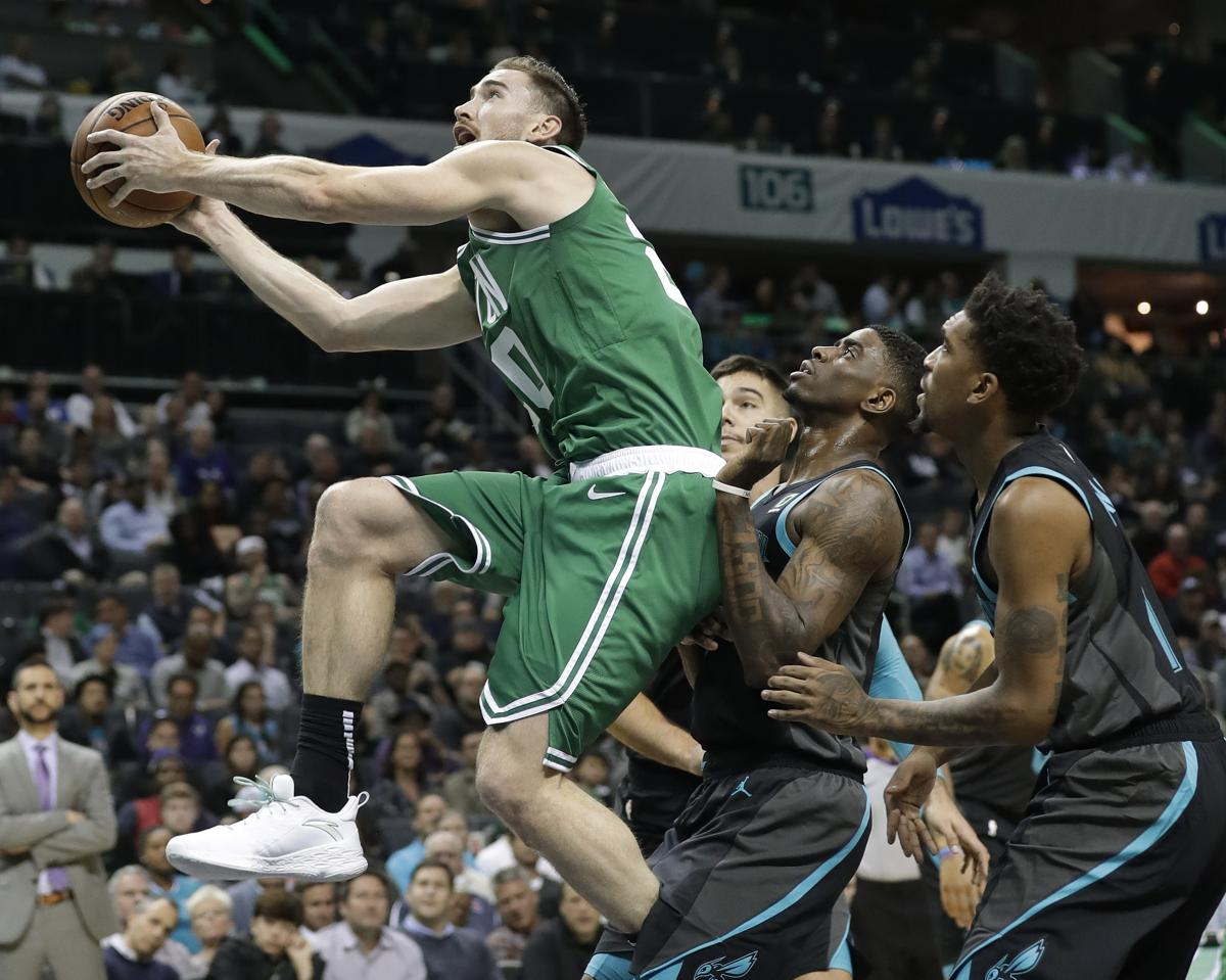 Boston Celtics Gordon Hayward, left, drives past Charlotte Hornets Malik  Monk,