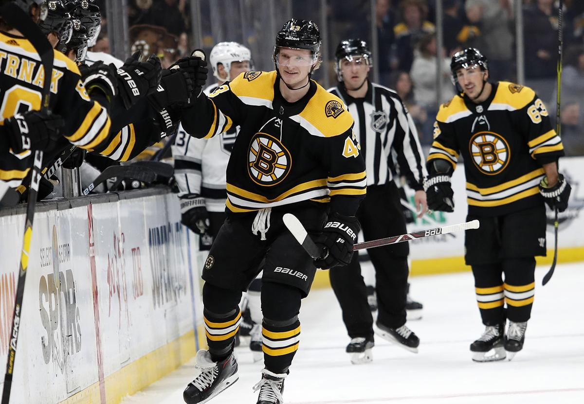 9c3caa30c37 Boston Bruins  Danton Heinen celebrates his goal with teammates on the  bench during the third