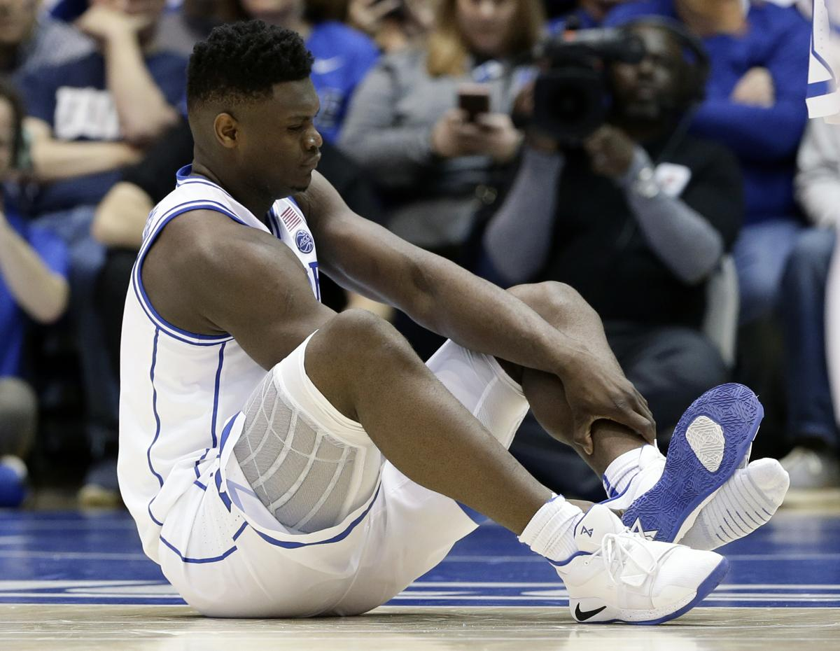 Duke s Zion Williamson sits on the floor following an injury during the  first half of an bb3883156