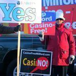 Guy Romano (left) and Nancy Wojick held opposing signs on the casino referendum outside a Milford polling place.