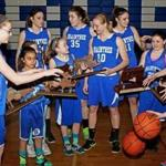 Brianna Herlihy, Molly Reagan, Ashley Russell, and Bridget Herlihy, members of the undefeated Braintree girls' basketball team, are surrounded by younger players they coach during a portrait.