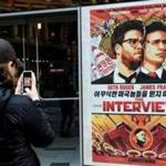 "A woman took a photo of a poster for the film, ""The Interview,"" outside of Regal Theater in New York in December 2014."