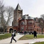 In this photo taken Wednesday April 6, 2016 students walk past the historic Thompson Hall at the University of New Hampshire in Durham, N.H. The water system serving the University is among more than two dozen in New Hampshire that have exceeded the federal lead standard at least once in the last three years. (AP Photo/Jim Cole)