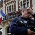 A policeman reacts as he secures a position in front of the city hall after two assailants had taken five people hostage in the church at Saint-Etienne-du -Rouvray near Rouen in Normandy, France, July 26, 2016. Two attackers killed a priest with a blade and seriously wounded another hostage in a church in northern France on Tuesday before being shot dead by French police. REUTERS/Pascal Rossignol