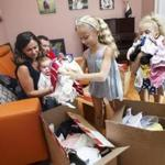 Chestnut Hill, MA - 09/15/2016 - Viktoriya(L) and Vlad(2nd L) Vilkomir hold their 10 month old son Gabriel as they watch their daughters Sophia(R),7, and Giselle(2nd R),9, pack gifts for donation at their home in Chestnut Hill, MA, September 15, 2016. (Keith Bedford/Globe Staff)