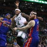 Boston, MA- 11-30-16: The Celtics Isaiah Thomas draws the defense of the Pistons Tobias Harris (left) and Aron Baynes (right), so he dished off the ball into the waiting hands of teammate Tyler Zeller (far right) on a first half drive to the basket. The Boston Celtics hosted the Detroit Pistons in a regular season NBA basketball game at the TD Garden. (Jim Davis/Globe Staff) reporter: himmelsbach topic: Celtics-Pistons
