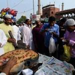 Indian Muslims sample seviyan, a sweet vermicelli dish, after offering prayers at a New Delhi mosque in June.