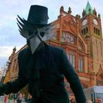A crow figure on stilts in Guildhall Square.