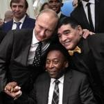 Russian President Vladimir Putin, Brazilian football legend Pele and Argentina's former midfielder Diego Maradona pose for pictures ahead of the Final Draw for the 2018 FIFA World Cup football tournament at the State Kremlin Palace in Moscow on December 01, 2017. / AFP PHOTO / SPUTNIK / Alexey NIKOLSKYALEXEY NIKOLSKY/AFP/Getty Images