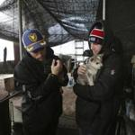 American freestyle skier Gus Kenworthy (left) and his boyfriend Matthew Wilkas held dogs Friday at a dog meat farm in Siheung, South Korea.