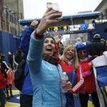 Boston, MA--4/15/2018-- Caitlin Burchill, of Salt Lake City, Utah (C) was doing a Facebook live post for her news station back in Salt Lake City as fellow Utah runners cheered from the Finish Line of the Boston Marathon. (Jessica Rinaldi/Globe Staff) Topic: 16marathoncolor Reporter: