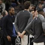 San Antonio Spurs forward Kawhi Leonard, left, listens during a team timeout during the second half of an NBA basketball game against the Memphis Grizzlies, Monday, March 5, 2018, in San Antonio. (AP Photo/Eric Gay)