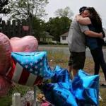 A couple embraced after leaving balloons at a memorial outside the home of Stewart Weldon.