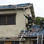 Firefighters check a house damaged by an earthquake in Ibaraki City, north of Osaka prefecture on June 18, 2018. A strong quake hit western Japan early June 18, but there were no immediate reports of major damage or risk of tsunami waves, officials said. / AFP PHOTO / JIJI PRESS / STR / Japan OUTSTR/AFP/Getty Images
