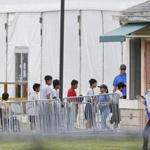 Immigrant children walk in a line outside the Homestead Temporary Shelter for Unaccompanied Children a former Job Corps site that now houses them, on Wednesday, June 20, 2018, in Homestead, Fla. U.S. Rep. Carlos Curbelo said he found it