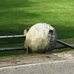 One of the spheres that was part of an art installation at Larz Anderson Park in Brookline lays damaged against a fence.  ​