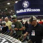 Attendees looked at a display of Smith and Wesson handguns during the NRA Annual Meeting & Exhibits at the Kay Bailey Hutchison Convention Center in Dallas.
