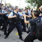 Members of the Chicago police department scuffle with an angry crowd at the scene of a police involved shooting in Chicago on Saturday.