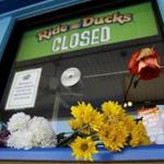 Flowers left by mourners rest on the ticket counter at the closed Ride the Ducks attraction Saturday in Branson, Mo.
