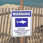 Kenneth Dutra was on duty at Longnook Beach. Warnings are posted about sharks and the possible danger of swimming.