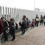 People lined up to cross into the United States to begin the process of applying for asylum near the San Ysidro port of entry in Tijuana, Mexico. A federal judge Friday called on the US government and the American Civil Liberties Union to come up with a plan to address the rights of parents and children to seek asylum.