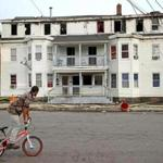 A bicyclist rode past a multi-family home on Springfield Street in Lawrence Friday.