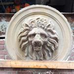 Crews carefully removed the lion's head from the Homans Building in Somerville as constuction of the MBTA Green Line extension continues.