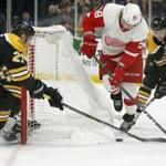 Detroit Red Wings left wing Tyler Bertuzzi (59) tries to move the puck around the net as Boston Bruins players John Moore (27) and Brandon Carlo (25) defend during the first period of an NHL hockey game, Saturday, Oct. 13, 2018, in Boston. (AP Photo/Mary Schwalm)